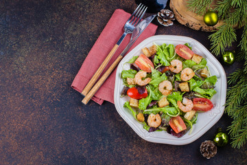 Fresh caesar salad with shrimps on white plate dark stone table background with Christmas Festive Decoration. Healhty Food Snack Concept. Top view Copy Space