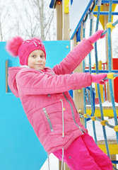 Cute little girl dressed in pink clothes plays on the playground outdoors in winter park