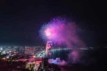 Multicolor fireworks night scene, blurred photo pattaya cityscape sea beach view, thailand