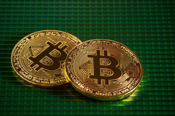Gold bitcoin on green Motherboard close up.  Bitcoin on the green surface of a solar battery.