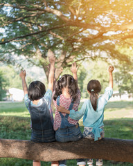 Happy kids in the park having fun sitting under tree shade playing together enjoying good memory and moment of girl student lifestyle with friends in school time day for children friendship concept