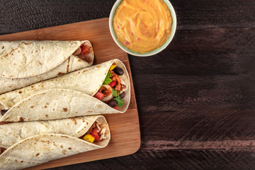 Mexican burritos with cheese salsa and copyspace, overhead shot
