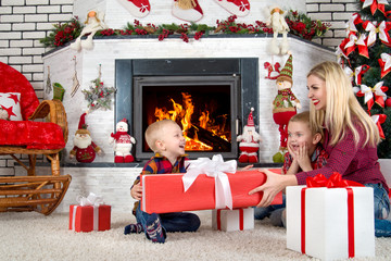 Merry Christmas and Happy Holidays!Mother and sons sitting by the fireplace and open Christmas gifts from Santa.
