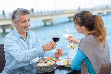 cheerful couple drinking wine and enjoying outdoors