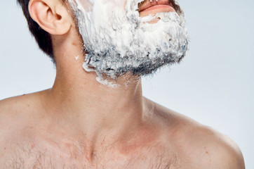 Young guy with beard on white isolated background in foam for shaving