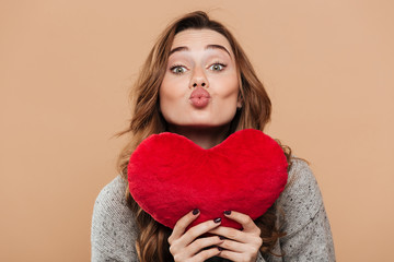 Close-up photo of lovely brunette girl holding big soft red heart while sending kiss, looking at camera