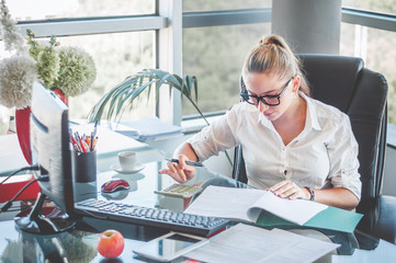 Portrait of young business lady in glasses sitting at her workplace and reads documents. Office worker at modern office workplace. Business concept.
