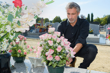 Foto auf Acrylglas Friedhof man putting fresh flowers in the graveyard