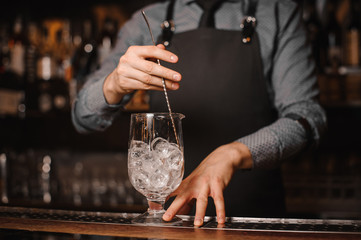 Bartender stirring ice cubes with help of spoon