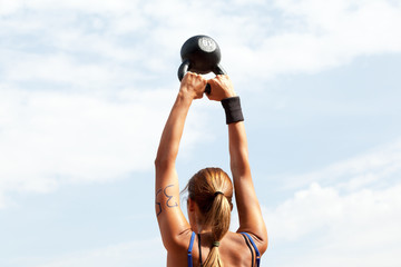 Female athlete doing kettlebell swings at crossfit competition