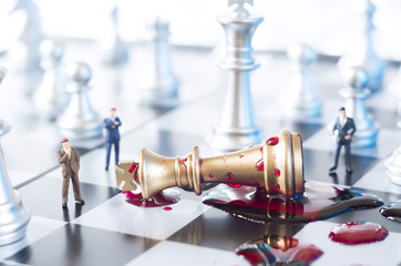 Conceptual photo with chess pieces, toy businessmen and blood on a chessboard. Business, law or political concept, which could represent war of corporations, geopolitical situation and so on.