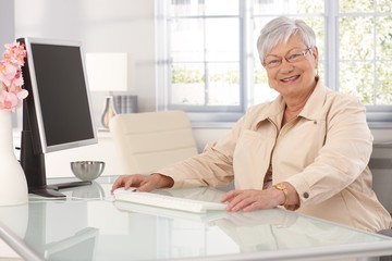 Happy old woman using computer at home