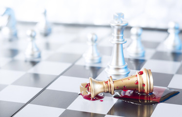 A conceptual photo with chess pieces and blood on a chessboard. Business, law or political concept, which could represent war of corporations, geopolitical situation and so on. Selective focus.