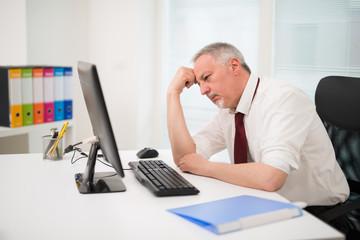 Sad businessman looking at his computer monitor