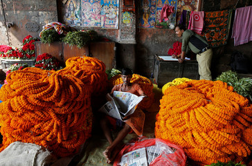 A man reads a newspaper next to marigold garlands, which are used to decorate temples and homes, at a wholesale flower market in Kolkata