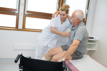 physiotherapist holding senior patient before wheelchair
