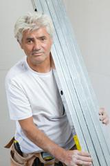 Builder holding square metal bars