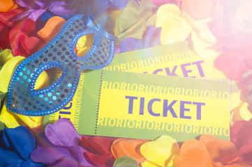 Brazil tickets sit with sparkly carnival mask on colorful flower lei background with party lens flare lighting