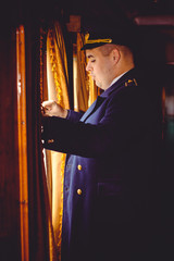 European or American train conductor is on his duty on a platform and other trains. Railway, steam trains, vintage trains .Train controller on the train, near a locomotive
