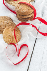 cookies, milk bottle on a white wooden background, and the heart of the red ribbon