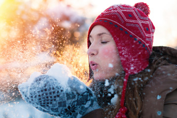 Beauty Winter Girl Blowing Snow in frosty winter Park - Flying Snowflakes - Sunny day - Backlit - Young woman Having Fun in Winter Park - Outdoors