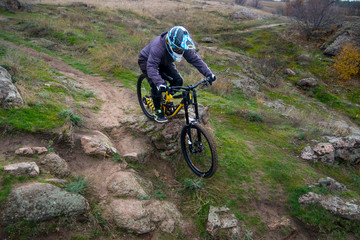 Professional Cyclist Riding Mountain Bike Down the Rocky Hill. Extreme Sport and Enduro Biking Concept.