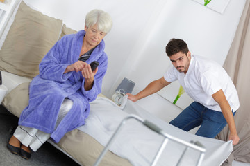 young male carer spending time with elderly woman