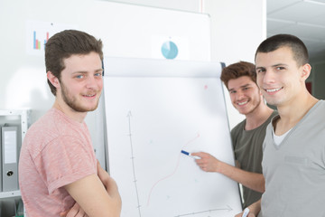 Young men showing graph on flip chart