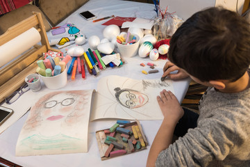 Young boy drawing with chalk surrounded with crufts and arts material, sitting at table