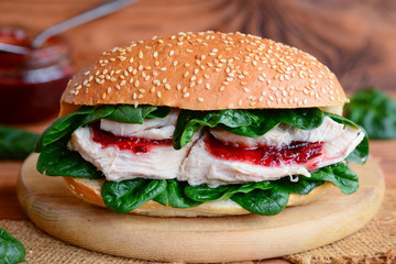 Crispy chicken fillet burger recipe. Simple chicken burger with fresh spinach and berry jam on a wooden board. Closeup