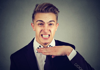 angry young man gesturing with hand to stop talking, cut it out. Negative emotion, feelings