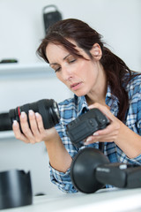 female photographer checking dslr fisheye camera lens