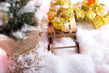 christmas tree with sledge and gold presents on white snow in winter