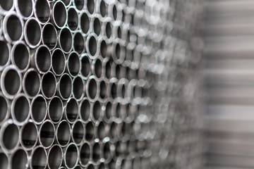 Industrial background. Close up of internal metal pipes in a warehouse. Stack of new and shiny steel pipe in factory.