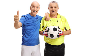 Elderly soccer player making a thumb up gesture and a goalkeeper with a football