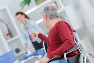 disabled patient pointing at beautiful healthcare worker