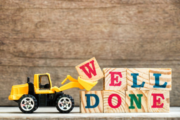 Toy bulldozer hold letter block w to complete word well done on wood background
