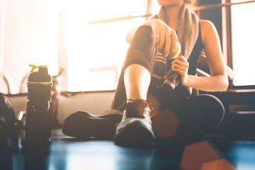 Sport woman sitting and resting after workout or exercise in fitness gym with protein shake or drinking water on floor. Relax concept. Strength training and Body build up theme. Warm and cool tone