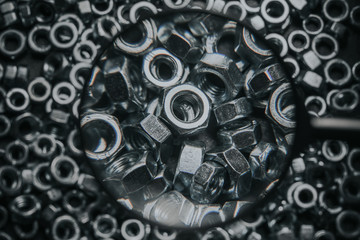 Metal nuts viewed through magnifying glass background.
