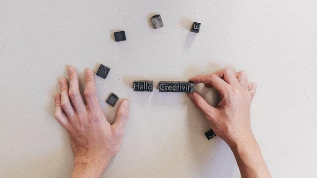 Crop man arranging printing letters