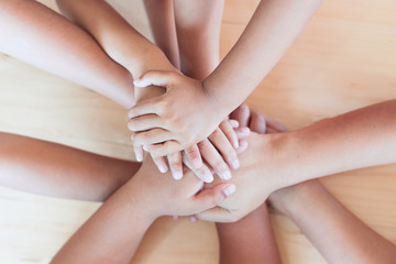 Parent and children holding hands together on wooden background. Family and friend stack hands showing unity and teamwork