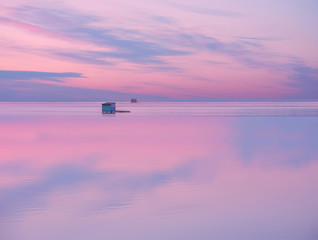 A small wooden house on the water's edge with the reflection of the sky in the water. Calm calm relaxing look on the evening sunset of the water surface and a lonely structure on the water.