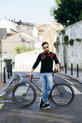 Stylish man with bicycle on street
