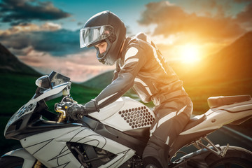 Motorcyclist on sport bike stands on the edge of the mountains in the background of a bright sunset.