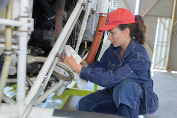 young woman mechanic working on machinery