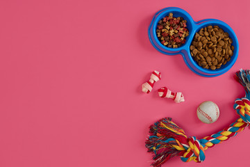 Toys -multi coloured rope, ball and dry food. Accessories for play on pink background top view