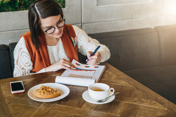 Young businesswoman in glasses and white sweater is sitting in cafe at table, working.Girl is looking at charts, graphs, diagrams. Girl analyzes data, plans, considers income. Student learning online.