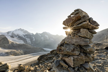 Cairn with sunray in the alps with glacier in the background, Diavolezza, Engandin, Switzerland