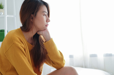 Pensive depressed young asian woman sitting and thinking on bed in the morning ,through the window