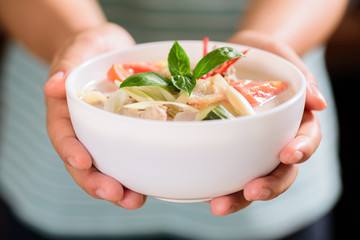 Thai food (Tom Kha Kai),Thai coconut milk soup with chicken in a bowl holding by hand
